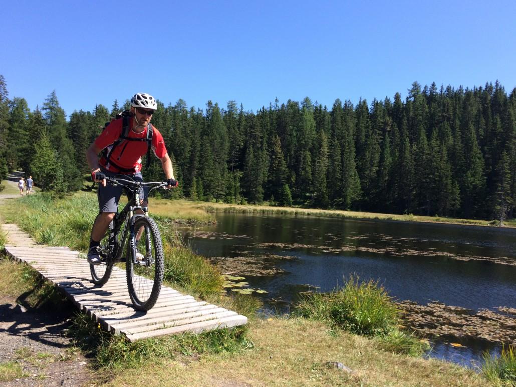 Ein Biker passiert einen Holzsteg an einem See
