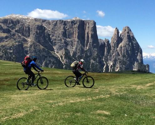 Biker fahren über eine Wiese mit einem Berg im Hintergrund
