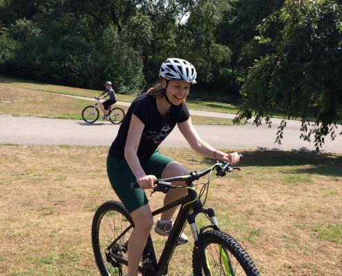 Eine Bikerin fährt beim Technik Training über eine Wiese