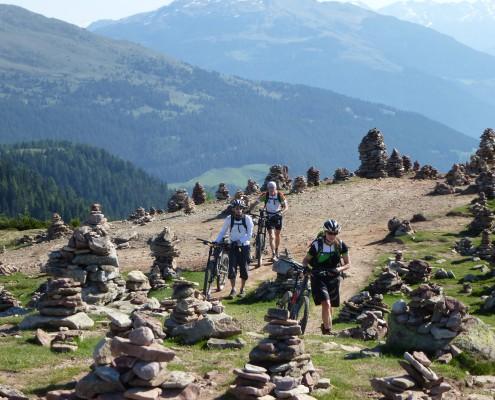 Die Gruppe schiebt ihre Bikes durch aufeinander gestapelte Steine