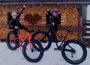 Mädels mit zwei Fatbikes vor einer Hütte